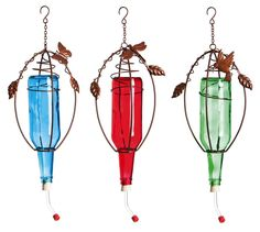 These colored glass bottle feeders will brighten any backyard space. and catch the attention of any roving hummingbirds! Bronze-colored metal detail is unique to each feeder, with butterfly, dragonfly and hummingbird decoration. Old Wine Bottles, Wine Bottle Candles, Recycled Glass Bottles, Wine Bottle Crafts, Bottle Art, Container Water Gardens, Wine Cork Art, Bottle Trees, Humming Bird Feeders
