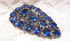 Shown here is a stunning vintage Art Deco blue glass stones dress/fur clip. All stones prong set and present. The stones are faceted and