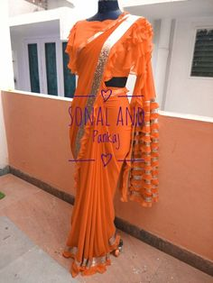 Shop VT- SONAL KI RUFFLE Sarees Online with the best price. Give yourself the stylish look for Rich Traditional Indian Wedding Parties. Saree Blouse Neck Designs, Fancy Blouse Designs, Blouse Patterns, Drape Sarees, Saree Tassels, Blouse Desings, Saree Jackets, Orange Saree, Stylish Sarees
