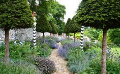 Topiary and oak are used in different ways throughout, and are softened with wild flowers or musky herb and herbaceous under-planting.  The poles with the chevrons are an Elizabethan device.
