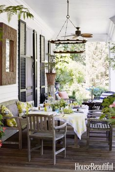 """COZY BENCHES – """"It's a true extension of the interior, with comfortable seating and a place to eat,"""" says Michael Maher of his porch. Fans and citronella candles repel insects from the unscreened space. Click for more patio ideas."""