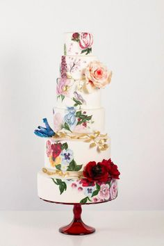 """Beautiful """"Secret Garden"""" Cake!  A mix of bold colored printed florals and three dimensional poppies, avalanche roses and striped parrot tulips -- wrapped with climbing golden laurel leaves.  Amazing detail and craftsmanship.  Cake by Nadia & Co."""