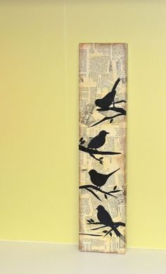 4 bird silhouettes on a newspaper background on a wooden board: