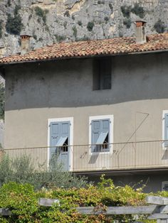 grey/blue shutters and taupe house.  I realize this is Italy and so of course we like it :)  Just not sure how it would translate with your home and your cool grey roof.