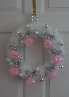 Beautiful Wreath.  No tutorial but it looks fairly easy to make.  Faux fur wrapped around a foam wreath, silver ribbon for bows, glass ornaments with some pink tulle inside and smaller silver and white ornaments for accents, hung with a beaded necklace.  So pretty.  I love the pink with the colors but for Christmas I'd probably do red.