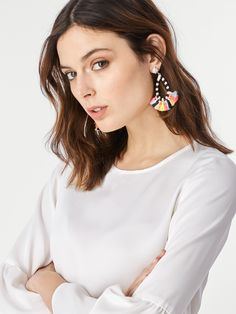 A colorful fringe lends the perfect measure of warmth and whimsy to monochromatic threading. Style with soft neutrals, such as an all-white ensemble.