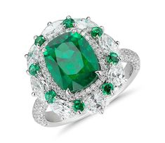 Grand doesn't begin to describe this one-of-a-kind ring. A breathtaking cushion-cut emerald is surrounded by a halo of pavé-set round brilliant diamonds, which is itself surrounded by a halo of alternating round emeralds and marquise-shaped diamonds. More pavé-set round brilliant diamonds adorn the band.