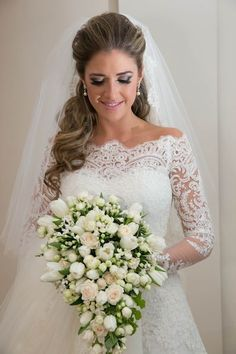A gorgeous lace wedding dress perfectly accented by a draping bouquet::