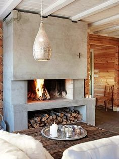 Love the contrast of the wood and concrete. Still looks warm and inviting. Plus a great way to store your wood. Fireplace.