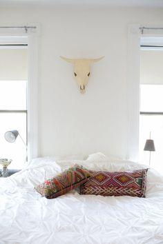 wielka czaszka + biała sypialnia + biała pościel + etniczne, wzorzyste poduszki w stylu boho