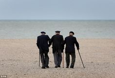 Poignant: Dunkirk veterans Michael Bentall (left), Arthur Taylor (centre) and James Baynes (right) walk arm in arm along the beach in Dunkirk to mark the 75th anniversary of the biggest military evacuation in history