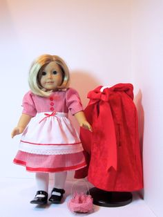 Little Red Riding Hood is wearing a gingham dress with red buttons and bows. The apron has an eyelet trim and ties in the back. She is wearing tights with black Mary Jane shoes. Her basket with more gingham is ready to go to Grandma's house.