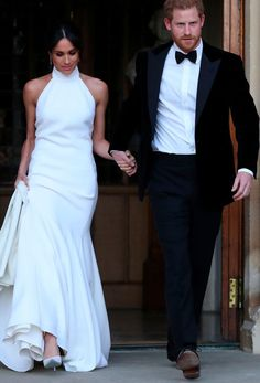 Meghan Markle second wedding dress by Stella McCartney. Prince Harry pictured in black tuxedo with bow tie. White halterneck wedding dress, side-parted up do, drop earrings.