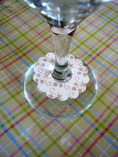 DIY Wine Charms • Use scrapbook paper, a large decorative punch and a small circle punch. By writing the guest's name on the 'charm' glasses cannot become confused.