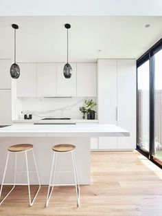 This renovated heritage cottage hides a modern interior This white kitchen features two black glass statement pendant lights over the white marble kitchen island. Pale timber flooring runs throughout. White Kitchen Interior, White Marble Kitchen, Home Decor Kitchen, Interior Design Kitchen, Home Design, Modern Interior, Home Kitchens, Design Ideas, Garage Interior