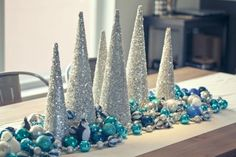 martha stewart christmas decorations - could do with the scrapbook paper, but I like the arrangement for the main table. Could get plastic dollar store ornaments for the rest or use garlands we may have Turquoise Christmas, Silver Christmas Decorations, Christmas Table Centerpieces, Coastal Christmas, Noel Christmas, White Christmas, Christmas Crafts, Elegant Christmas, Centerpiece Ideas
