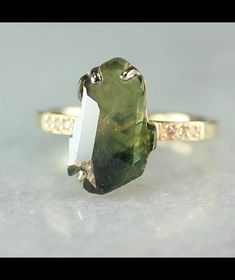 This ring features a one-of-a-kind, partially hand-cut and polished, 3.86 carat green sapphire. The stripes within the gem are a result of the sapphire's natural growth pattern of chevron-shaped crystal structures. One of a kind. Six 1.2mm brilliant white diamonds have been bead-set into the band on each side of the sapphire. The ring is 14k recycled yellow gold and is available in a polished finish, as pictured, or a brushed (matte) finish.