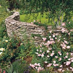 An undulating stone wall creates a barrier while looking stylish at the same time. Fieldstone offers a natural material for garden walls. You can either dry stack stone or use mortar to hold it together. (Dry-stacked walls should be no taller than 4 feet.) For a natural garden backdrop, a stone wall offers a classic and long-lasting option./