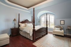 Master bedroom decked out in baby blue, with cherry wood flooring and dark wood four post bed frame with matching side dresser.