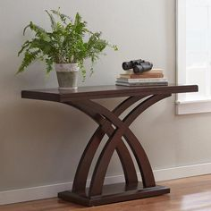 A curved x-shaped base fuses with a rich cherry finish to round out this eye-catching console table. Use it add sophisticated style to the living room then top it off with shimmering objets d'art for a dynamic display. Wood Table Decor, Table Design, Decor, Wood Table Design, Furniture, Coffee Table Design, Woodworking Furniture Plans, Home Decor Furniture, Console Table Decorating