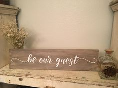 Hand painted wood sign, be our guest. Rustic home decor sign created to bring warmth, joy, and happiness into your home.  -This sign in 24 long x 5 1/2 high x 3/4 wide. -Pine wood. -Paint. -Wood stain. -Hand painted letters with white paint. -Clear top coat. -Includes a D-Ring hanger on the back to hang on the wall.  These signs are made to order, stained and painted by hand. It also has a clear coat on top, but I do not recommend hanging it outside. No two signs will ever look exac...