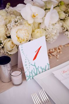 Table number cards printed in coral and light turquoise match the menus set at each guest's place.