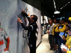 Na loja da Nike, Alberto assina mural do Santos FC. Atletas da Escolinha assistem o evento atentamente.