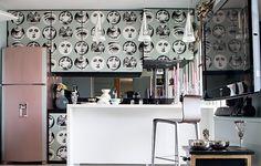 Se você quase não usa a cozinha, como a interior stylist Melany Kuperman, não importa que ela seja minúscula. Aproveite para usar elementos raramente vistos no ambiente, como papel de parede. A geladeira pintada de rosa completa a decoração