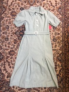 Go dust bowl chic with this adorable dress of the 1930s! Big white buttons and a tidy little belt make this dress quite the charmer. Cotton. Just the sweetest!  Size small! Repair on front of skirt of lower left hand pleat. Very small head of pin-sized hole on back of skirt. A couple of very tiny dot stains occur sporadically on the back of the garment. Small rust colored staining on the hip of the garment. Bust: 16 inches across Waist: 26 inches Hip: 17 inches across Arm opening: 4 1/2 ...