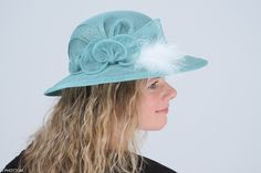 Adrienn is a charming formal hat with a stylish composition complemented with a delicate feathers at a side. This headpiece is hand formed and sewed, making it an exclusive design. This artisan cocktail hat would be a perfect ladies headwear at a wedding or other special occasion.