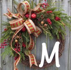This Christmas Monogram wreath is characterized by extremely realistic greenery, berries, and apples. The gorgeous bow is made from a plaid faux