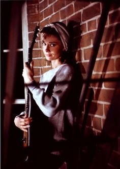 """Audrey Hepburn Playing Guitar in Breakfast at Tiffany's  This is not some Beatnik serenading her neighbors from the window of her """"pad."""" The wistful lass strumming the guitar is Audrey Hepburn, who is rarely seen on the screen in anything but the latest fashions. She plays the slightly zany Holly Golightly in Paramount's film version of Breakfast at Tiffany's."""