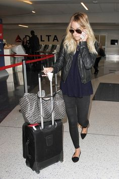 Lauren Conrad wears black jeans and a moto jacket with flats and aviator sunglasses.