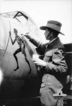 Sussex, England. c. 1944-08. Australian war artist, Dennis Adams paints a typically australian design on the fuselage of the Mosquito aircraft flown by 404891 Wing Commander G. Panitz DFC, Southport, QLD, commanding officer of No. 464 (Mosquito)squadron RAAF with the second tactical air force at RAF station Thorney Island.
