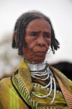 Africa | Portrait of an elderly Borana woman.  South Ethiopia | In Borana culture men can have several wives. The traditional leather clothing and the typical collars made of cubic metallic beads are now quickly being replaced by woven clothing and plastic collars. | © Geert Henau