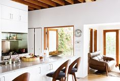 Bright kitchen with modern stools and adjacent sitting area with leather sofa