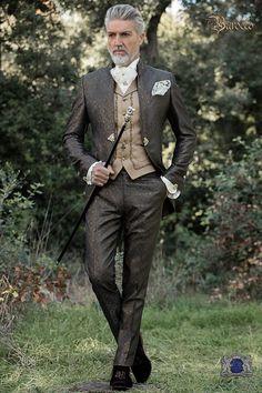 Costume de marié baroque en tissu jacquard gris-or. Ce costume vintage est une redingote avec des broderies en d'or, Napoléon col, une poche sur la poitrine, des poches avec des rabats élégants et une broche de fermeture. Numéro de modèle: 2066 Collection Baroque.