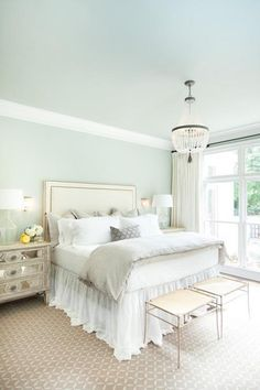 Cream and blue bedroom features a blue ceiling over blue walls lined with a cream headboard with antique brass nailhead trim on bed dressed in white and gray linen bedding as well as a white ruffled bedskirt flanked by mirrored chests as nightstands topped with clear glass lamps alongside a pair of cream brass stools placed at the foot of the bed atop a taupe geometric rug illuminated by a clear beaded chandelier.