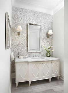 White and gray bathroom features a gray mosaic tiled accent wall lined with a white washstand ...