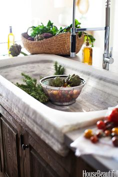 The natural striation of the stone in this marble kitchen sink brings an element of artful sophistication. Plus, we're absolutely in love with this wide and shallow shape. Click through for more design ideas for kitchen and bathroom sinks.