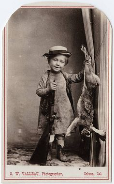 Turn of the Century photograph of a young child with a shot gun and a dead rabbit...