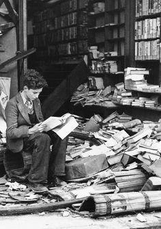 """A boy sits amid the ruins of a London bookshop following an air raid on October 8, 1940, reading a book titled """"The History of London""""."""