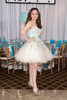 A pretty Bat Mitzvah dress with beautiful appliqués and an accent ribbon and broach which tied the whole look together from Castle Couture.