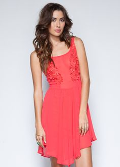Spring into the new season in this flowy sun dress. Features lace flower detail at front with an asymetrical cut and back zipper closure.    100% polyester  28 length  Model is wearing size S