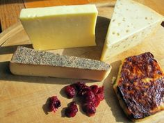 """Cheese is a source of pride among many Wisconsinites, nicknamed """"cheeseheads."""" More than 600 varieties are made in the state, including, from upper left, aged cheddar, gouda with fennel, Juustoleipa cheese with jalapenos and Sartori Black Pepper BellaVitano. Dried cranberries represent another prominent Wisconsin offering."""
