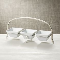 A simple, stylish design to serve condiments, snacks, desserts, appetizers and toppings, this gift-registry favorite presents a trio of rectangular bowls on a silver-finished iron base.