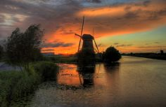 Holland: Sunset over the water at Kinderdijk. Kinderdijk village has 19 windmills that tourists may visit any time of year. There is no admission fee of any kind, except for a small museum. Try to visit when they are operating (every Saturday in June & July - ask locally). You may learn about their operation. One mill is always open for viewing throughout the year.