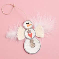 Metal-Rim Tag Snowman Ornament, cut out wings and glue glitter to wings, buttons and feathers hot-glued to embellish. Don't forget eyes and nose.