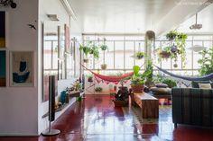 Bem iluminada, essa sala permite que a moradora tenha um verdadeiro jardim dentro de casa.