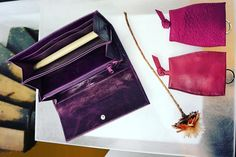 Still life in our shop. Ladies wallet made of purple goatskin and 2 key pouches made of cowhide.